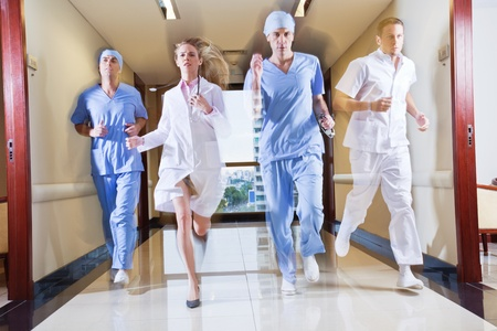 Doctor and nurse running in hallway of hospital photo