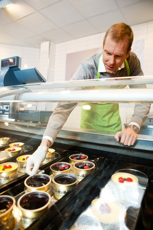 fancy cake: A man selling gourmet deserts from behind a glass counter