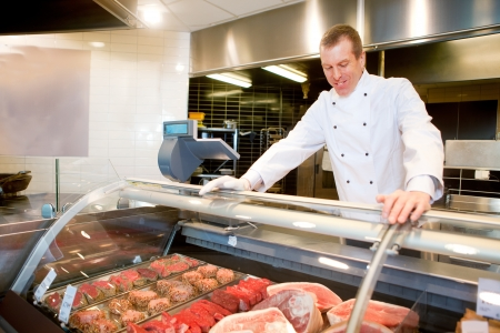carnicero: Un carnicero en un mostrador de carne fresca en una tienda de abarrotes