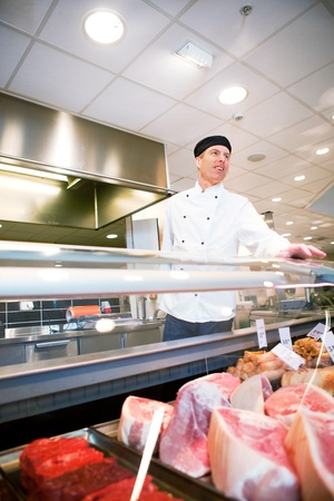meat counter: A butcher helping a customer at a fresh meat counter or deli