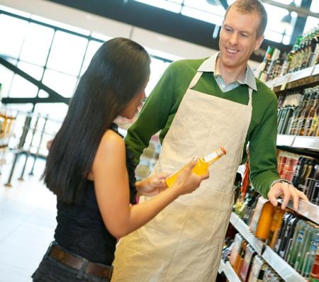 oficinista: Mujer de pie con sonriente tienda trabajador mientras mantiene la botella de la bebida en la tienda de abarrotes