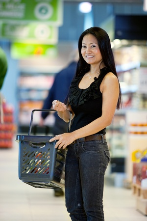 superstore: A happy female asian woman with grocery basket in supermarket
