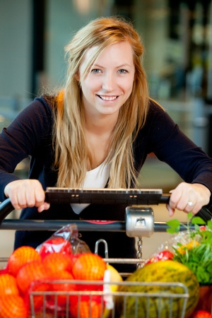 A happy shopping woman with grocery cart full of fruits and vegetables Stock Photo - 10033298