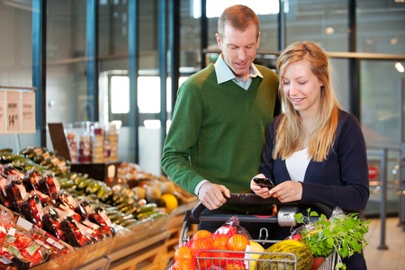 mall interior: A happy couple buying groceries looking at grocery list on phone