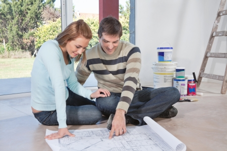 home renovation: Mature man showing blueprint of their new house to his wife Stock Photo