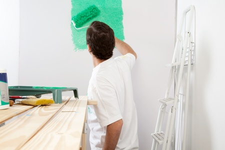 house renovation: Man painting the wall with roller and brush, stepladder in background Stock Photo