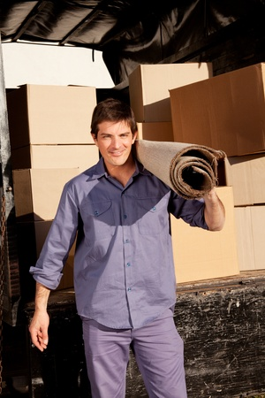 A portrait of a professional mover with a carpet and boxes in the background photo