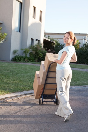 shifting: Portrait of an pretty woman with stack of box moving to a new house