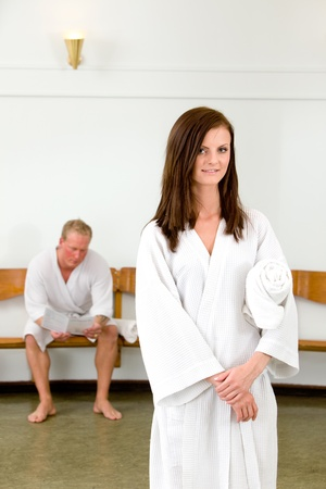 portrait of a woman looking at the camera in a wellness spa, with a man waiting in the background photo