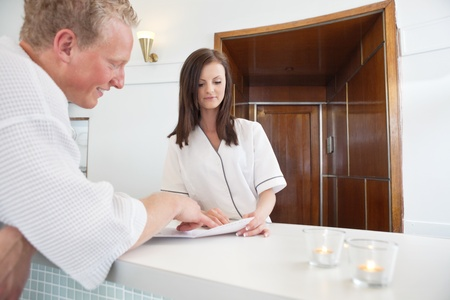 Mature man standing at a spa reception deciding on a treatment photo
