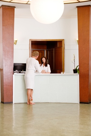desk clerk: A functionalism (funkis) spa interior with a man choosing a therapy package