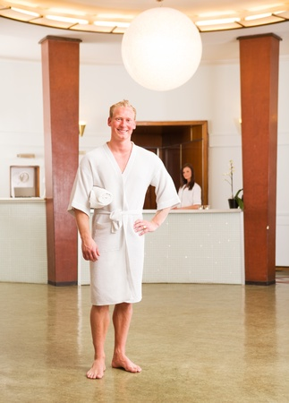A man in a bathrobe standing in a reception of a spa, looking at the camera photo