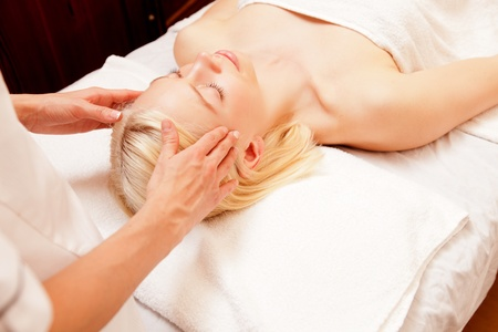 A pretty young woman receiving a scalp massage in a spa photo