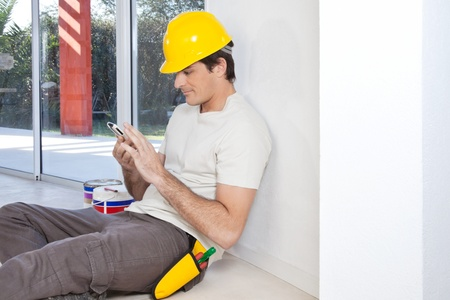 Construction worker looking in cellphone while sitting photo