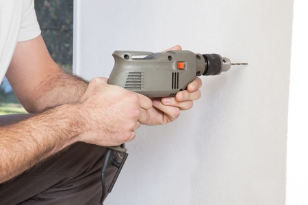 electric drill: Close-up of human hand holding drilling machine