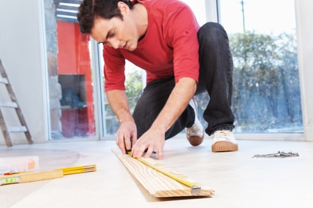 Architect measuring the wooden plank with measuring tape photo