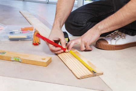 Man marking on plywood with measuring and pencil photo