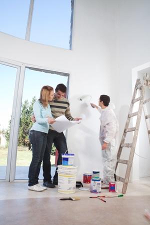 彼らの家の塗り替え作業中の青写真を見て若いカップル 写真素材
