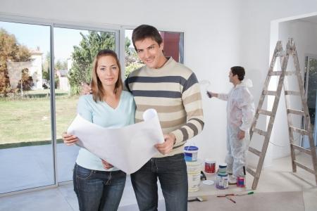 pintor de casas: Retrato de la feliz pareja sonriendo con el pintor en segundo plano Foto de archivo