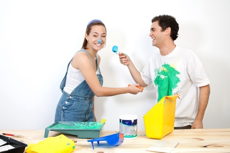 man painting: Cheerful couple doing mischief with paint