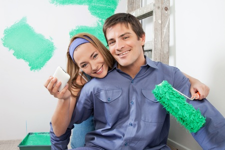 refurbish: Portrait of smiling couple holding mobile phone and color roller Stock Photo
