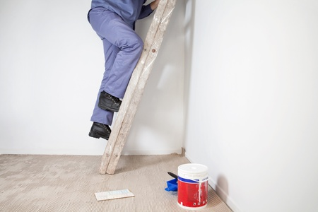 Low section of mans legs climbing wooden ladder photo