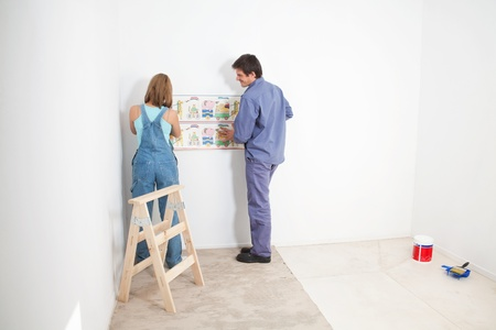 Couple putting up wall papper in baby room photo