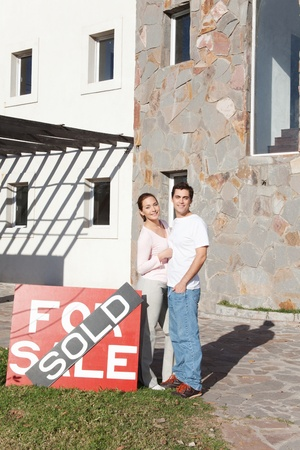 Couple standing near house sold sign outside home photo