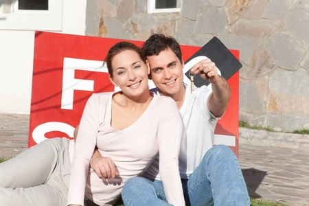 Portrait of smiling man holding keys with wife sitting on side Stock Photo - 10041212