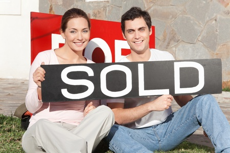 Happy couple sitting against their new house with sold sign photo