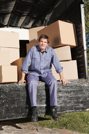 moving van: Thoughtful man sitting in the truck with pile of boxes behind him