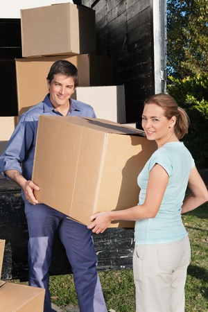 Smiling couple moving boxes at their new home photo