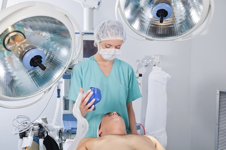 Doctor applying oxygen mask on patient before operation Stock Photo - 10127177