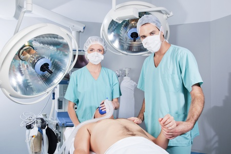 Female doctor applying gas and male doctor checking pulse rate of patient Stock Photo - 10127255