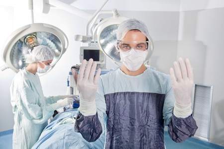 Male surgeon asking for gloves in middle of operation Stock Photo - 10127195