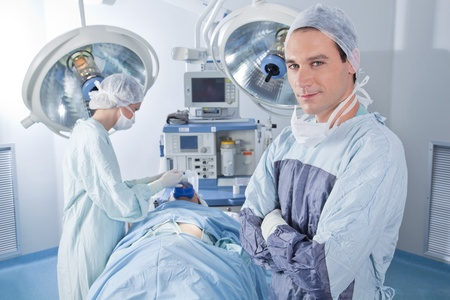surgery room: Smiling male doctor with arms crossed in operating room