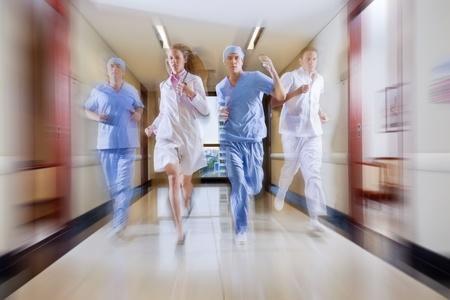 Surgeon and nurse running in hallway of hospital photo