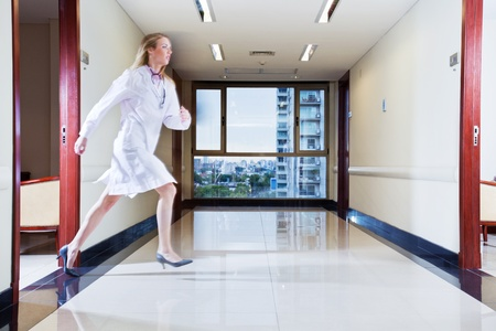 Female doctor rushing across the hallway in hospital photo
