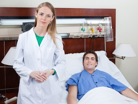 Portrait of confident young female doctor with patient in hospital photo