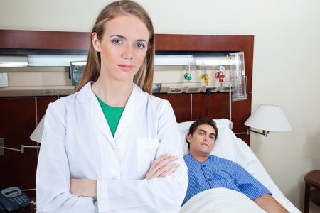 poised: Young female doctor in hospital with patient lying on bed in background