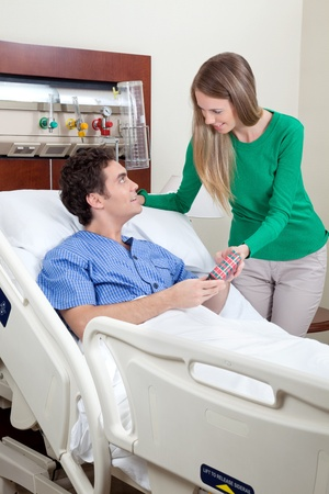 Smiling patient receiving gift from beautiful wife Stock Photo - 10127238