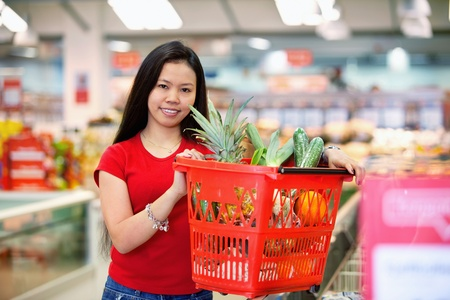Smiling woman holding basket filled with fruits in shopping centre and looking at camera photo