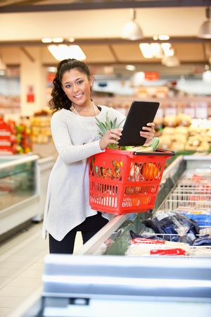 Shopper with basket holding digital tablet and looking at camera photo