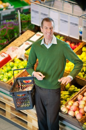 Mid adult man carrying shopping basket and looking at camera while shopping in fruit store photo