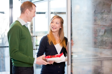 A happy couple choosing groceries from the frozen food section in a supermarket photo