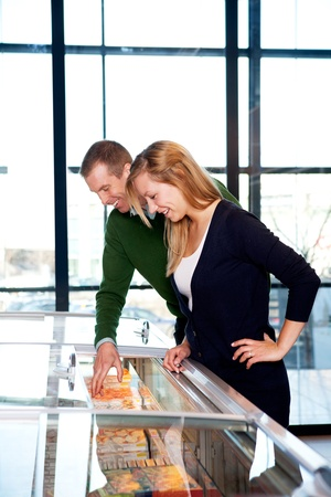 A happy couple in a supermarket buying frozen food photo