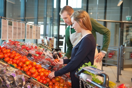 Woman holding tomato while standing with shop worker in grocery store photo
