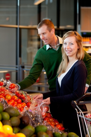 A happy couple buying fruit and vegetables in a supermarket photo