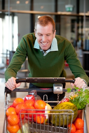 Portrait of a man pushing a grocery cart in a grocery store photo