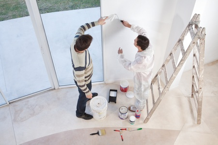 Young man showing a spot on the wall to painter photo